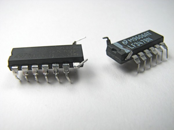 A pair of microchips with two legs bent up to look like bugs or defects