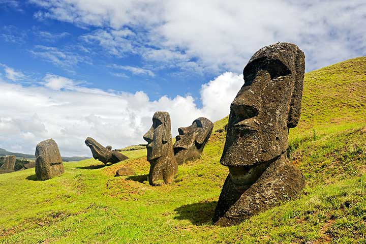 Destinations Worth Dreaming Image: Five moai are visible—three are upright; one is tilted forward, and another is tilted back.
