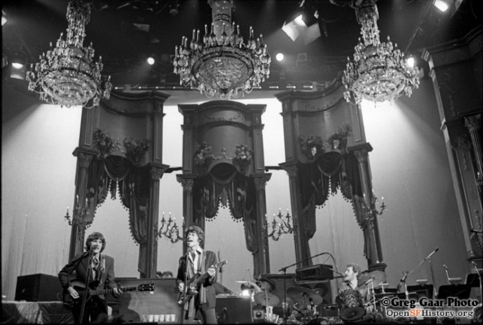 Black and white photograph of The Band playing on the Winterland stage under chandeliers.
