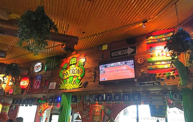 Interior decor of Tijuana Taxi Co, banners, signs, pinata cacti, tv