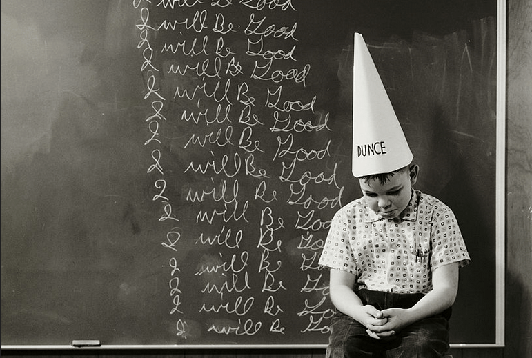 "A kid in a dunce cap in front of a chalkboard on which he has written ""I will be good"" numerous times"
