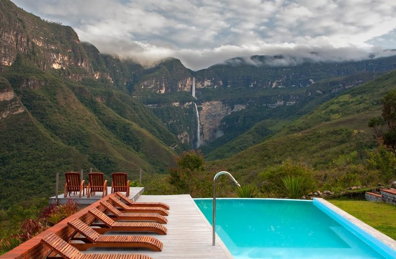 Best Hikes In Peru Image: A hotel swimming pool is surrounded by wooden lounge chairs, and offers an incredible view of the waterfall at the other end of this mountainous landscape.