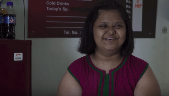 An image of Aditi smiling widely as she looks to the side. On the wall behind her we can see a menu.