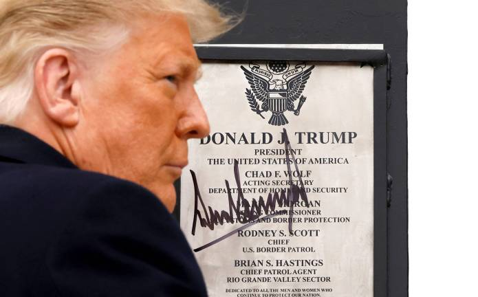 U.S. President Donald Trump signs a plaque placed at the U.S.-Mexico border wall during his visit, in Alamo, Texas, on Tuesday. | REUTERS