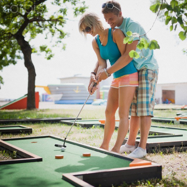 Young couple playing mini golf