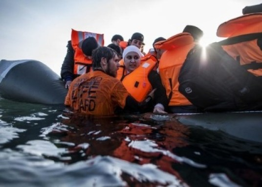 A Syrian refugee is helped by a volunteer to leave a sinking dinghy at a beach on the southeastern island of Lesbos, Sunday, Feb. 28, 2016. Greece is mired in a full-blown diplomatic dispute with some EU countries over their border slowdowns and closures. Those border moves have left Greece and the migrants caught between an increasingly fractious Europe, where several countries are reluctant to accept more asylum-seekers, and Turkey, which has appeared unwilling or unable to staunch the torrent of people leaving in barely seaworthy smuggling boats for Greek islands. (AP Photo/Manu Brabo)