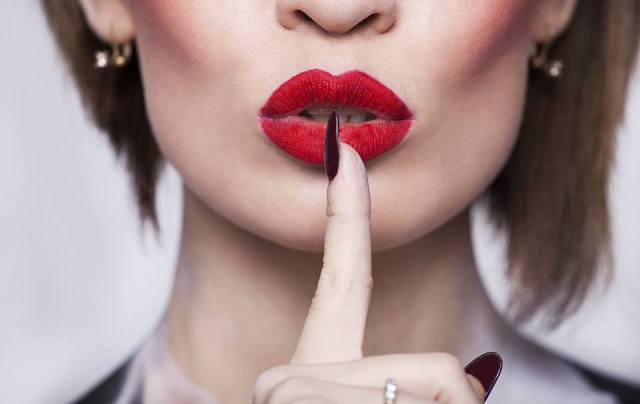 Woman red lips with finger shh
