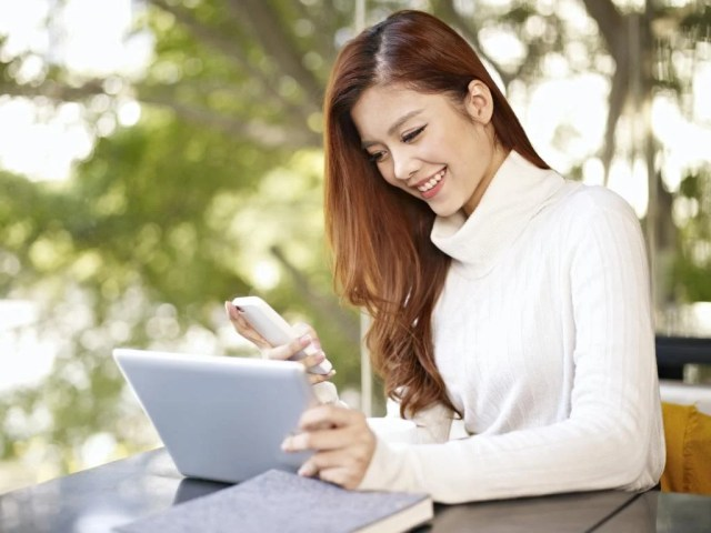 asian young woman working with mobile phone and tablet computer in coffee shop.
