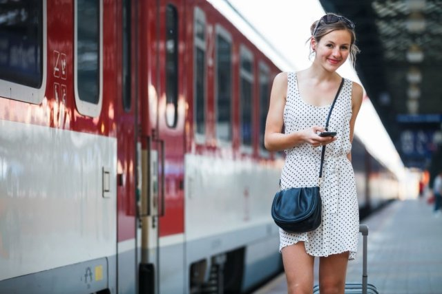 Girl-with-cell-phone-and-suitcase-next-to-train