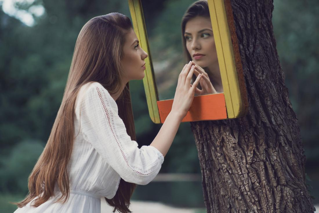 woman staring at herself in a mirror