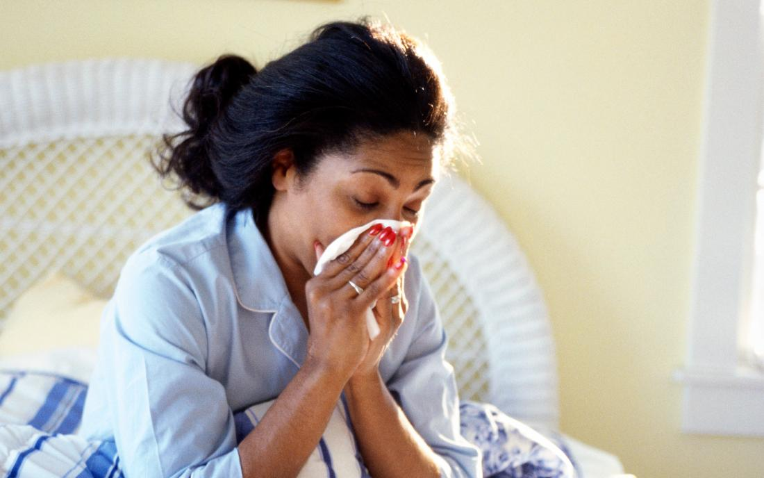 a woman sat in bed and blowing her nose because she has the flu.