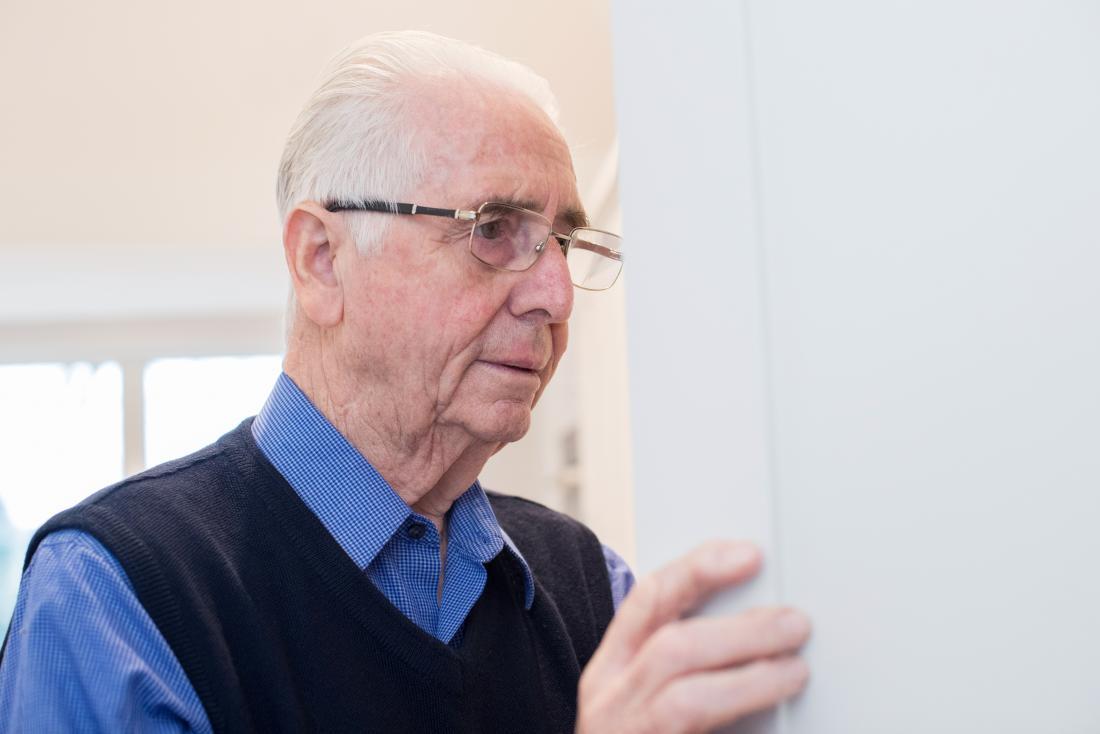Senior man looking into cupboard