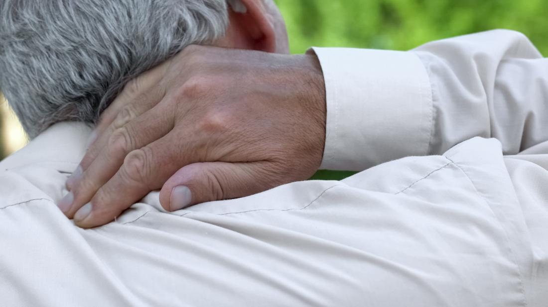 a man holding the back of his neck because he is experiencing pain there