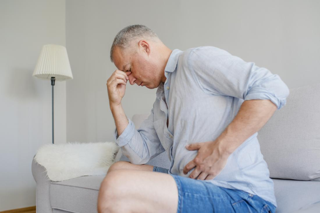 Man with acid reflux holding stomach in pain