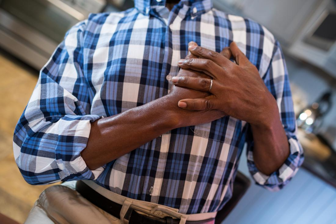 Man holding hands over heart because of chest pain attack