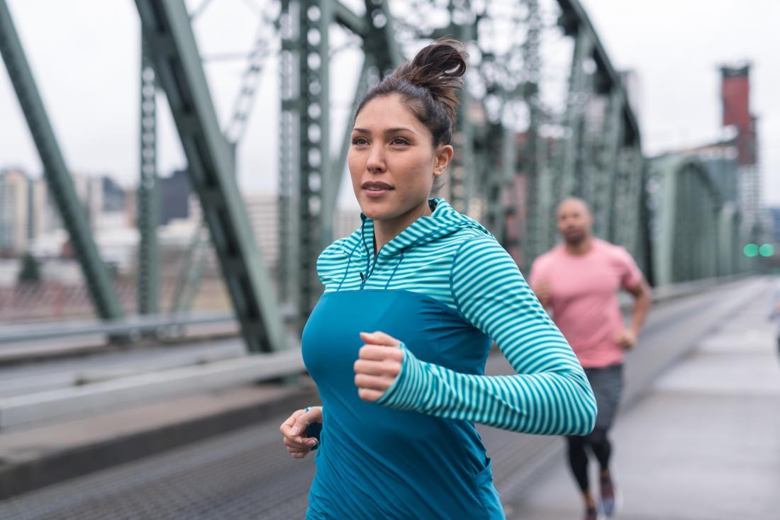 Woman and man running or jogging on bridge