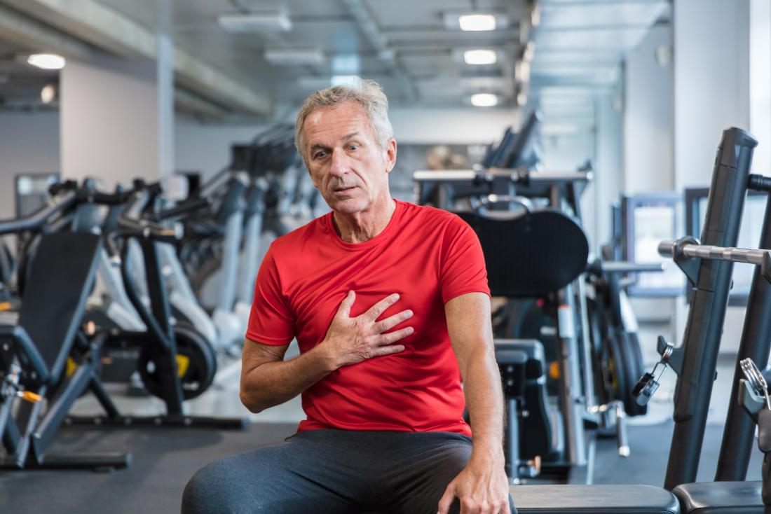 Man in gym holding chest in pain because of heart failure.