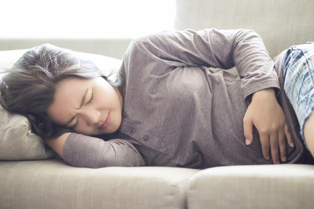 woman with pelvic pain holding stomach while laying on side.