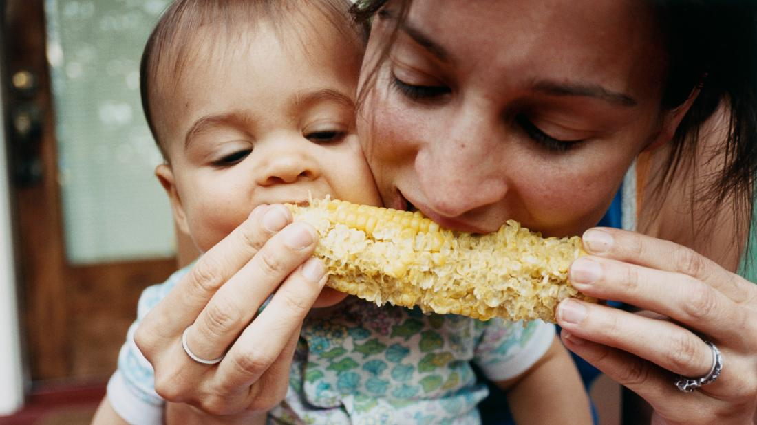 a mother and baby eating a corn of the cobb for good Nutrition