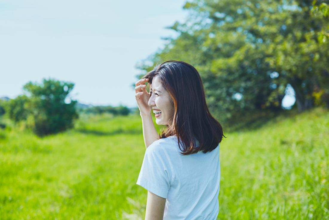 a woman looking happy in a sunny field.