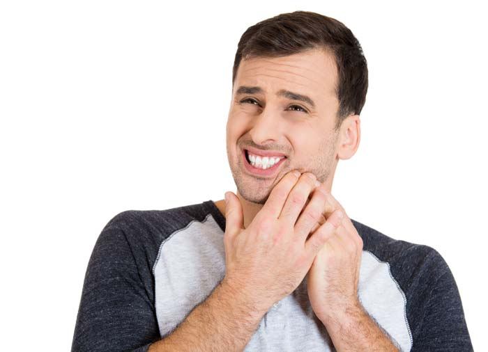 A man holding his mouth, suffering with dental pain