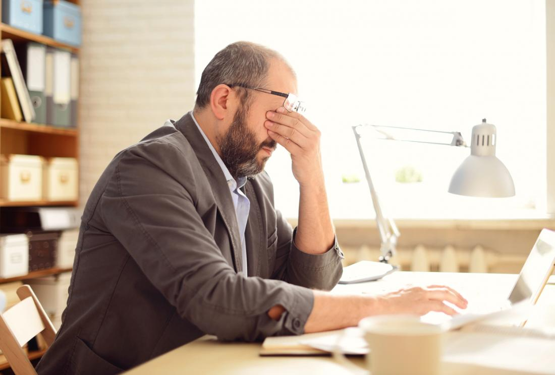 man sitting at desk rubbing his eyes stressed and with a headache