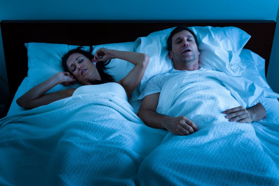 Man snoring in bed while woman is annoyed