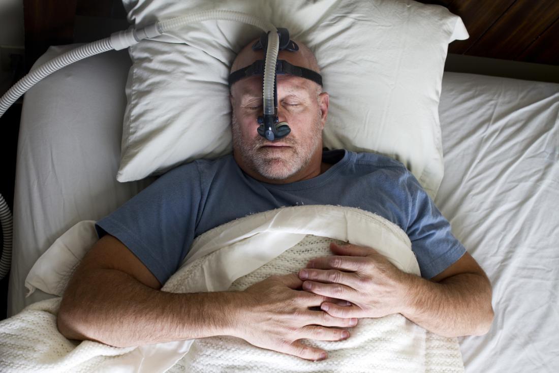 戴着CPAP治疗面罩睡着的人。