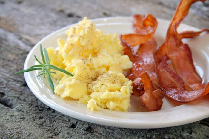 Scrambled eggs and bacon on plate.