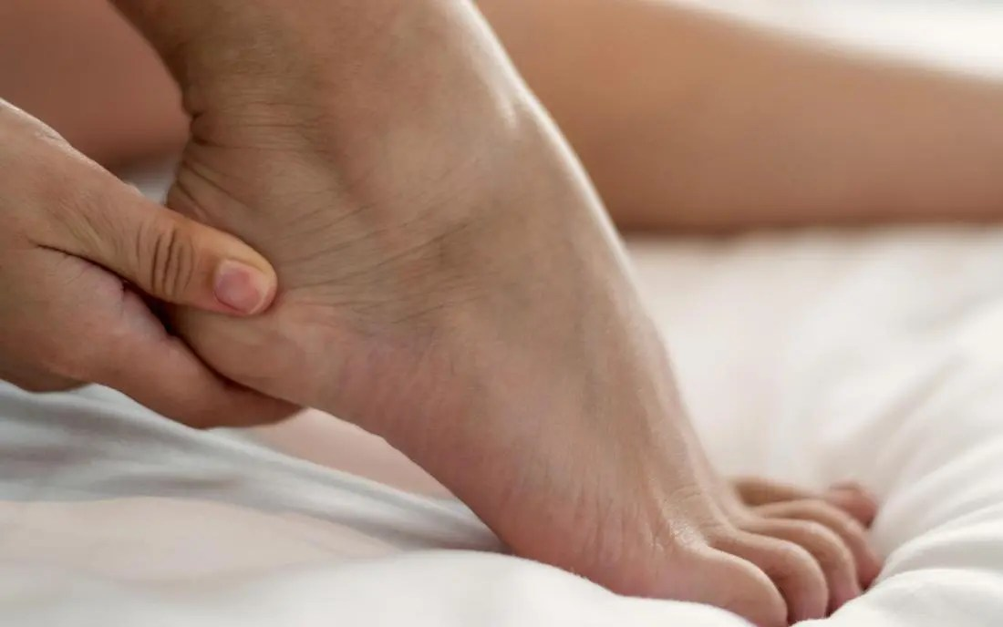 a person holds their foot because of heel pain.