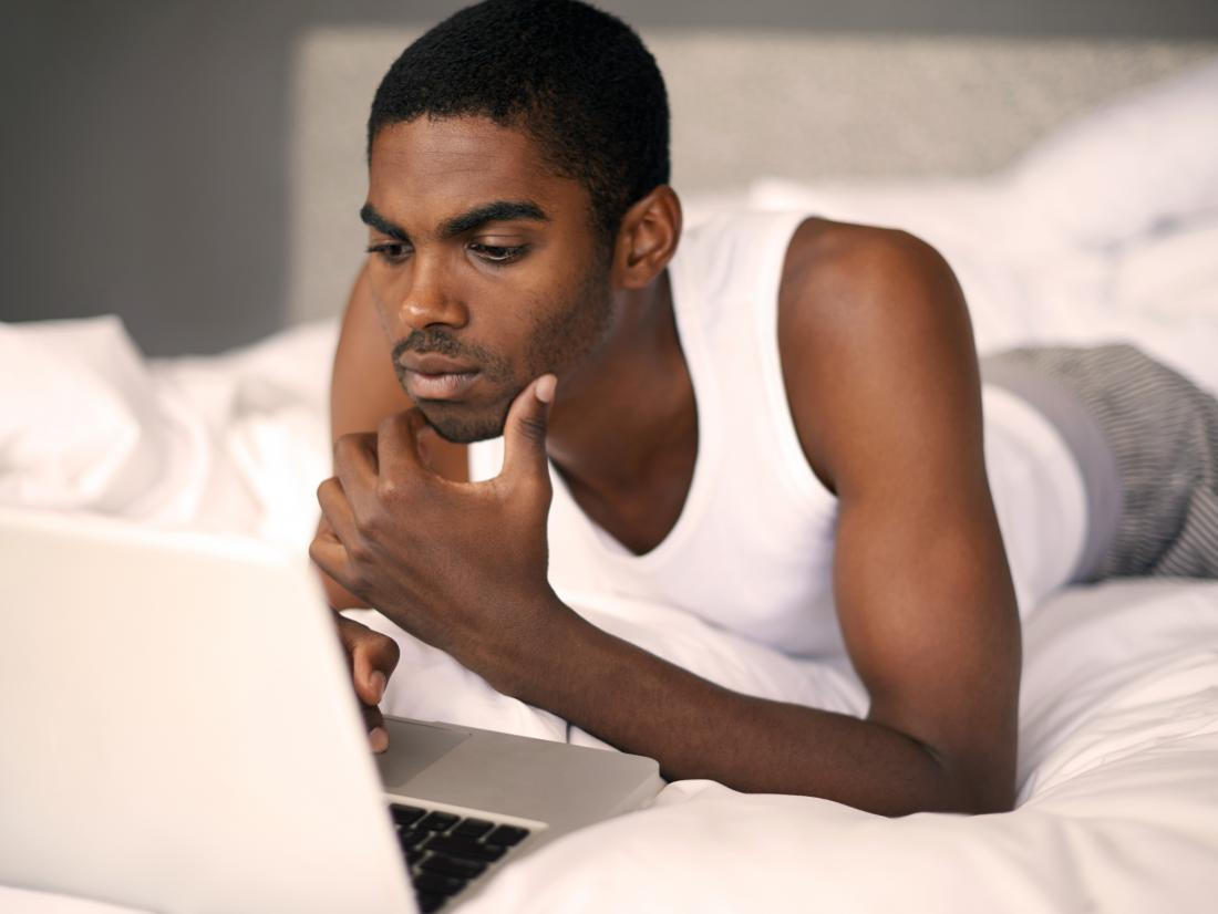 a man lying on his bed whilst on a laptop.