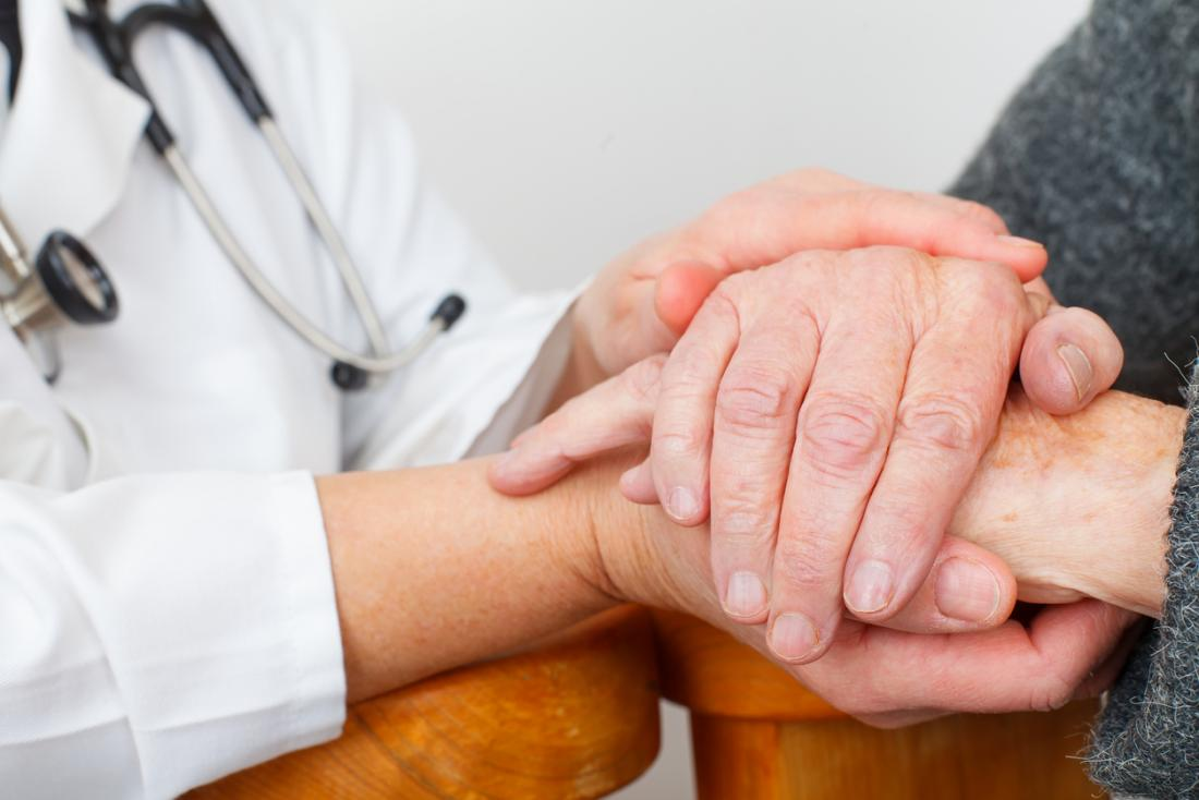 patient and doctor hold hands