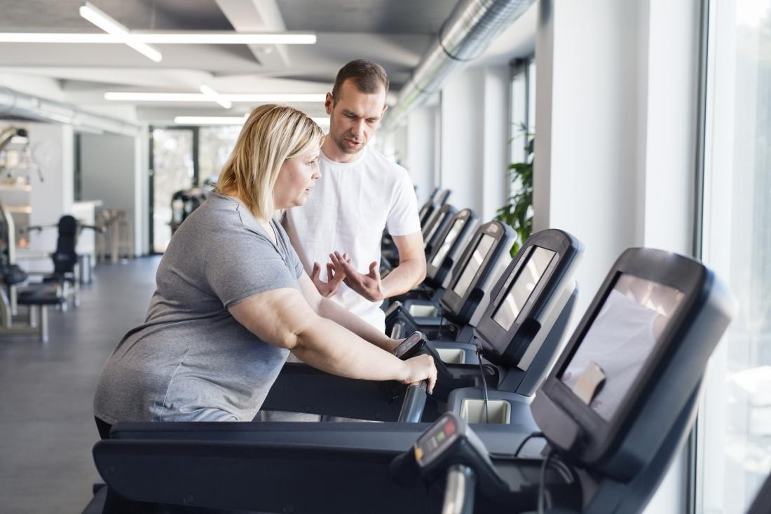 Obese or overweight woman exercising on running machine treadmill in gym with person trainer for weight loss
