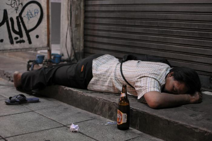 A man passed out in the street from alcohol consumption.