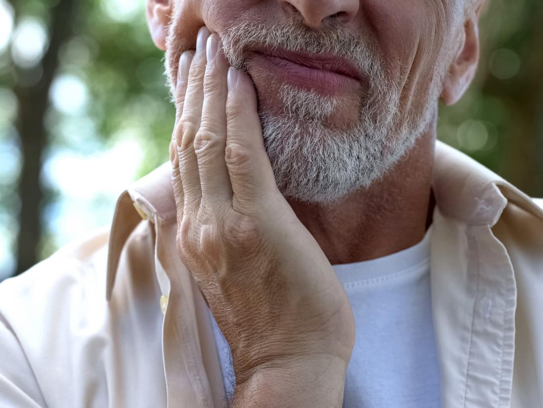 a man holding his jaw as he is suffering from salivary gland cancer