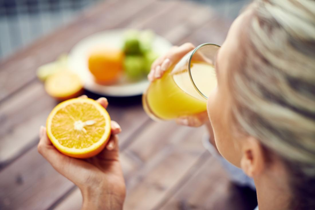a woman drinking orange juice and holding an orange.