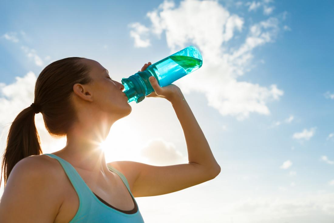 Woman drinking from hard plastic bottle.