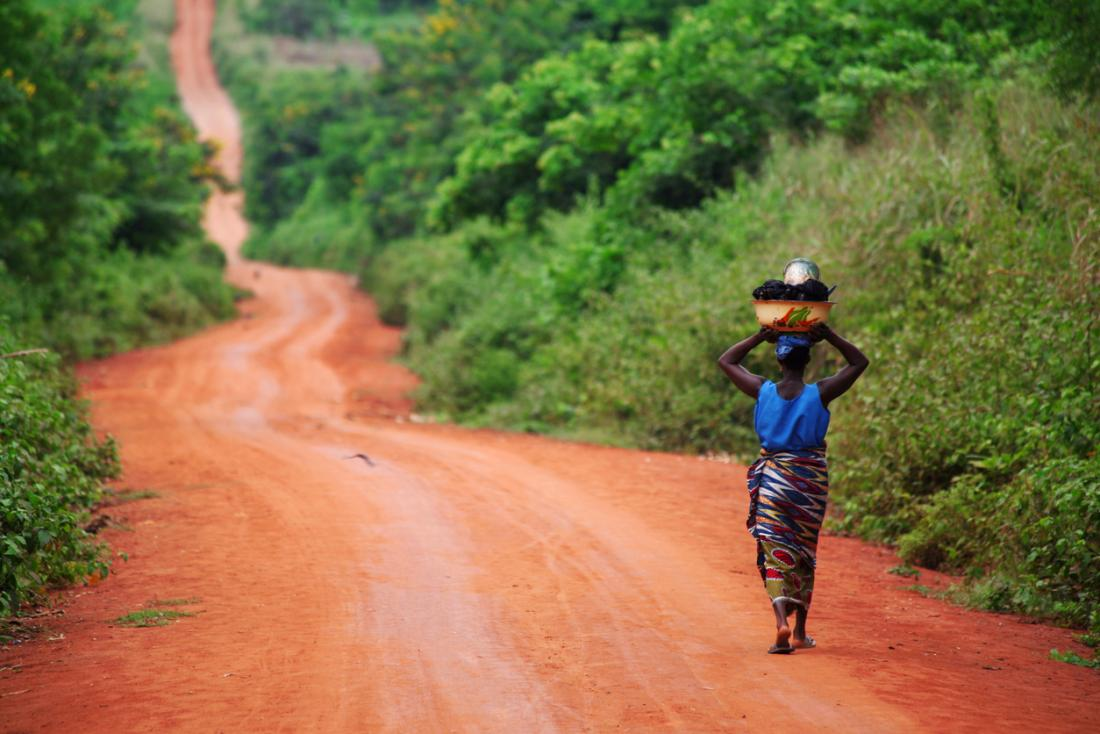 African woman walking along a dirt road.