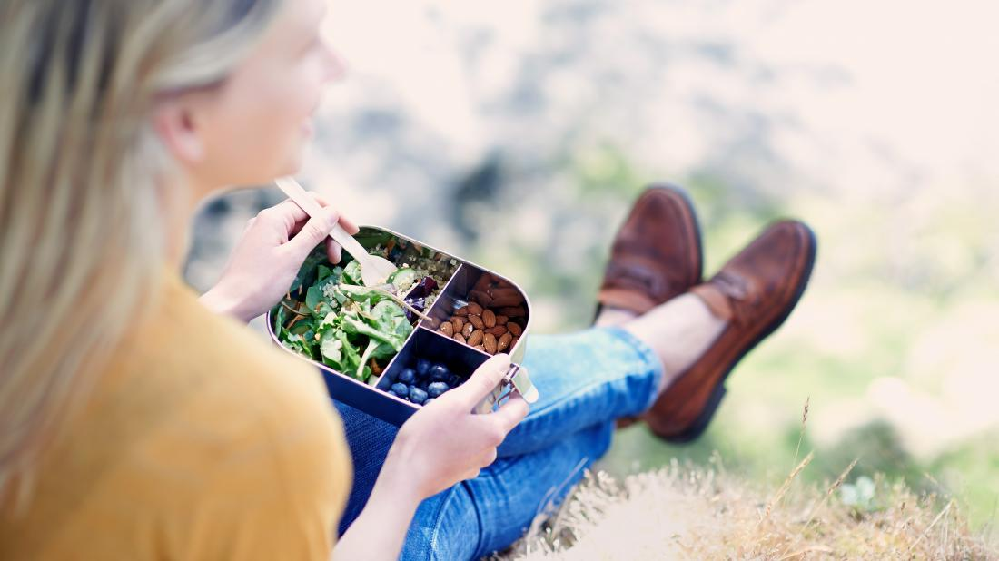 a woman sat outside and eating some of the most healthful food