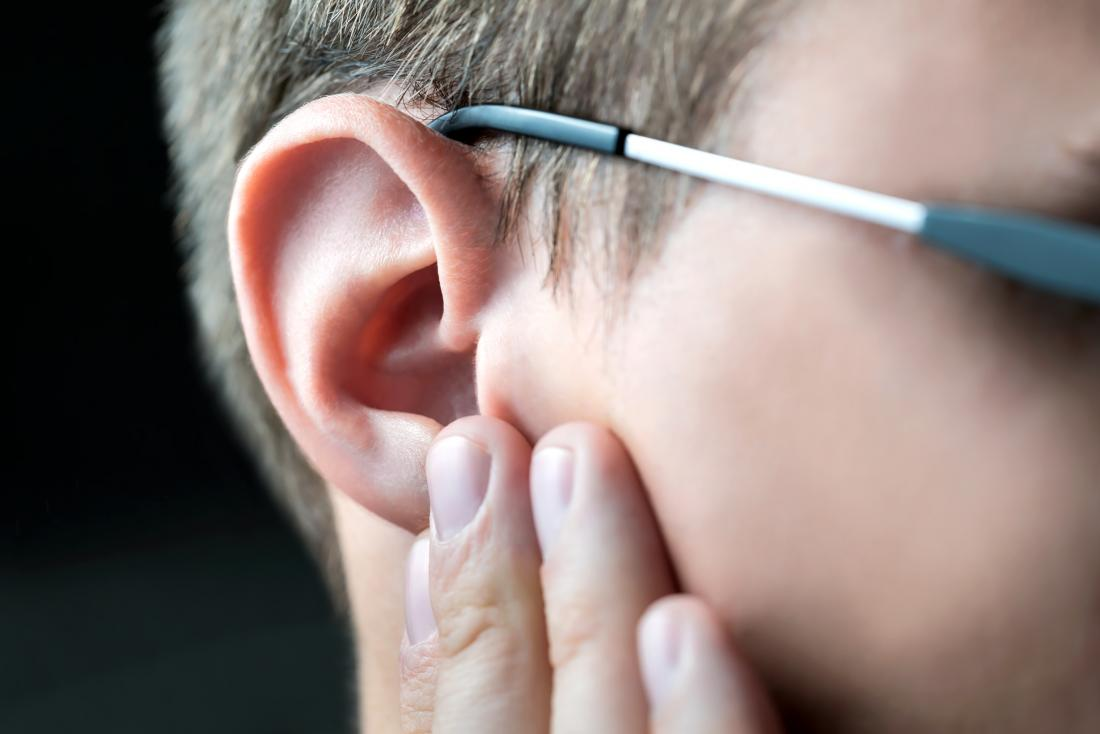 Person touching ear considering otoplasty