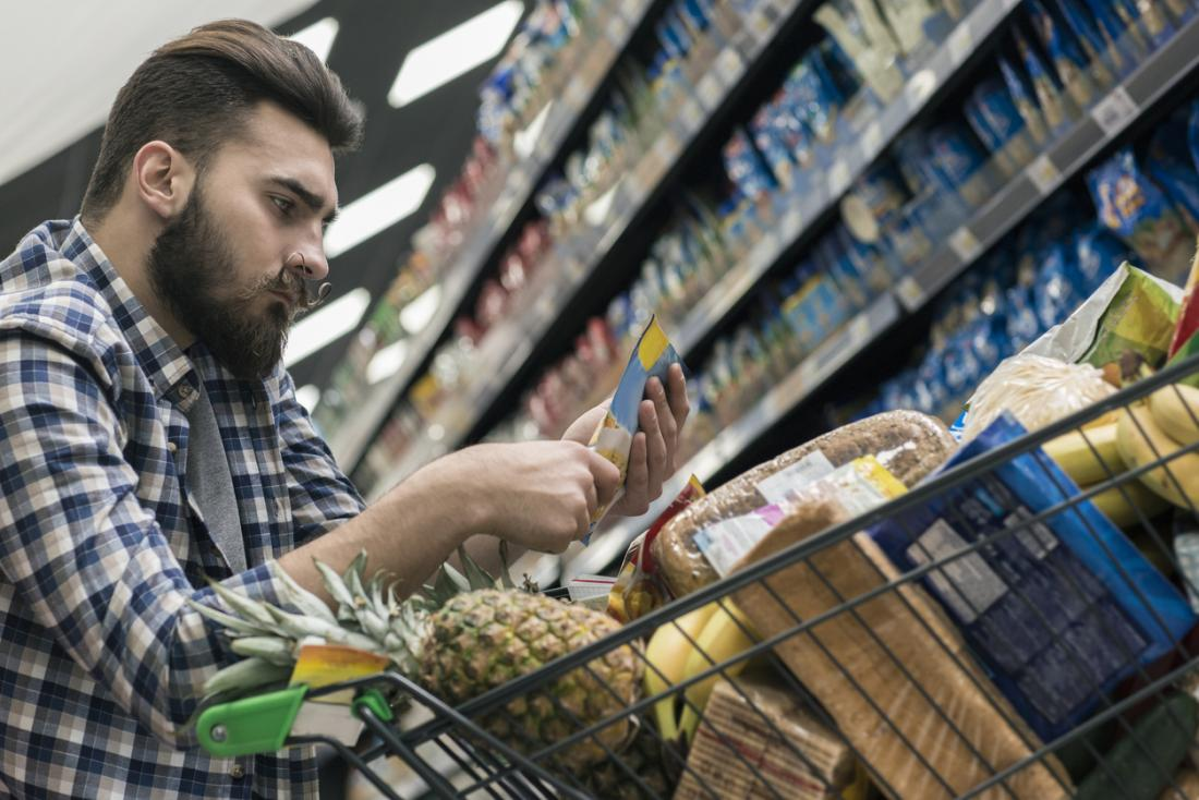 Man looks at nutritional information while shopping