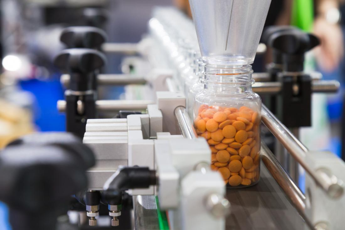 Bottles of medication pills or pharmaceutical drugs being made in factory production line.