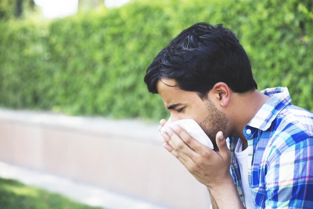 Man blows nose outside