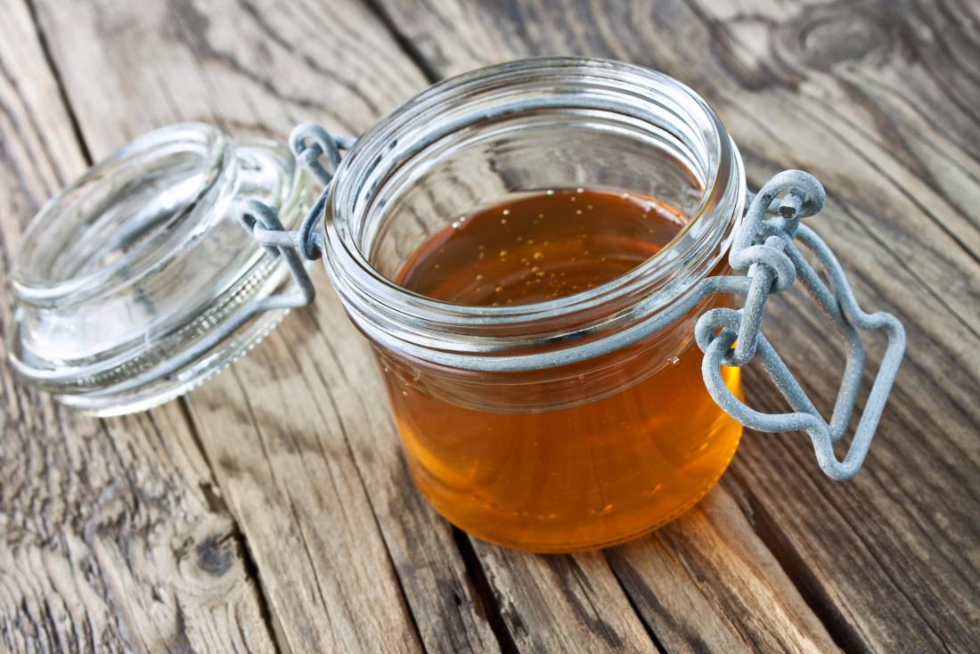 a Honey and jar against wooden background