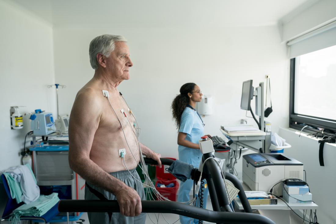Person performing cardiovascular stress test on treadmill or running machine.
