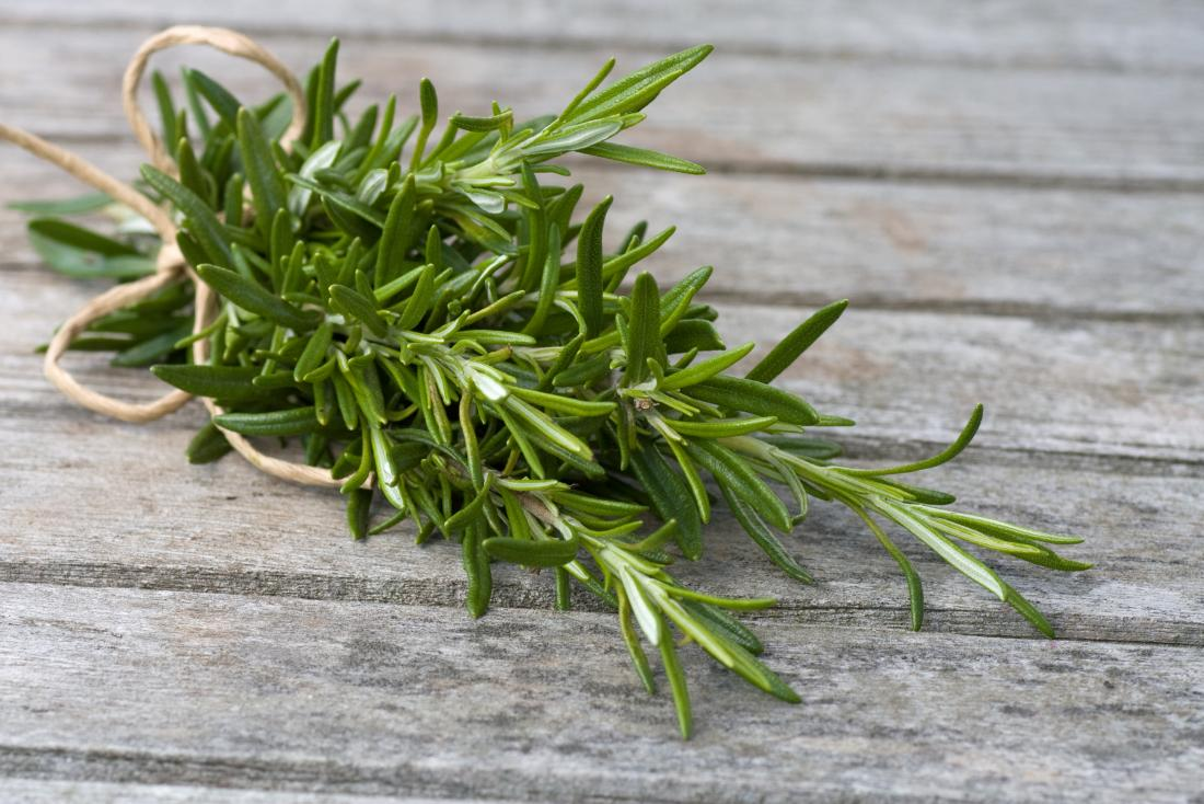 Rosemary leaves bound in rope on wooden table