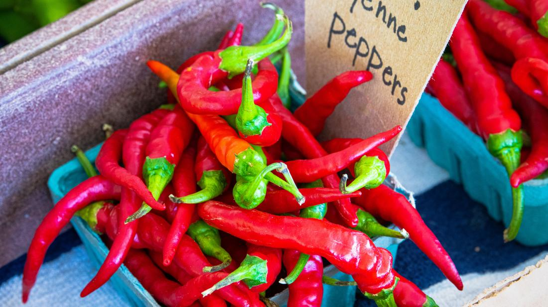 whole cayenne peppers on a food stand.