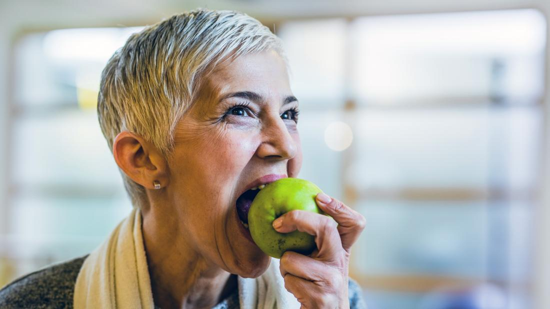 a woman eating a green apple.