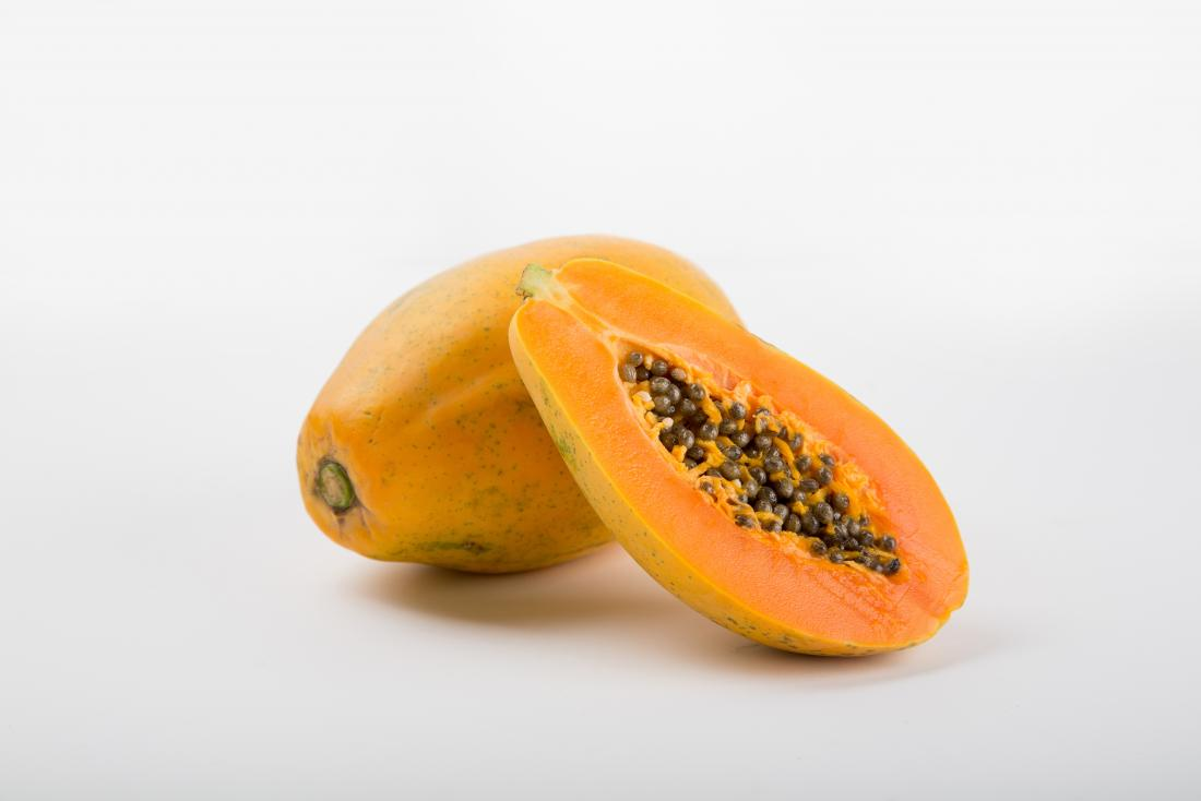 Papaya fruit cut in half with seeds showing.