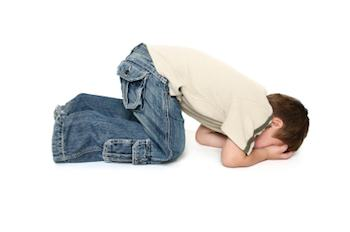 Child kneeling on the floor, hiding his face
